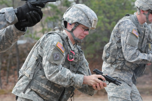 Staff Sgt. Christopher Williams, 441th Engineer Company, 467th Engineer Battalion, 926th Engineer Brigade, performs a magazine exchange while in a crouched stance during the M9 pistol qualification range for the 412th Theater Engineer Command's 2013 Best Warrior Competition held at Fort Devens, Mass. April 24.