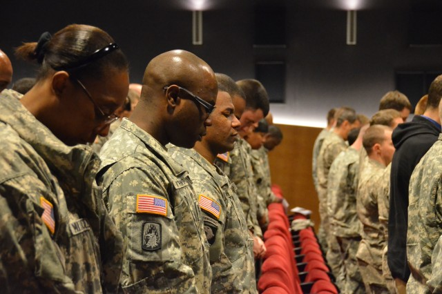 Soldiers bow their heads in prayer during the invocation of the U.S. Army Garrison Ansbach Days of Remembrance ceremony at Katterbach Theater April 19, 2013.