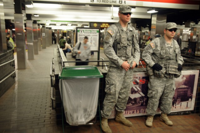 Spc. Matthew Martin from Medford, Mass., and Spc. Jason Manni, from Peabody, Mass., both Soldiers with Headquarters Company, 1st Battalion, 182nd Infantry Regiment, stand at the entrance to the Park Street MBTA station to randomly check baggage and ensure public safety for Boston residents and commuters, Boston, April 16, 2013.