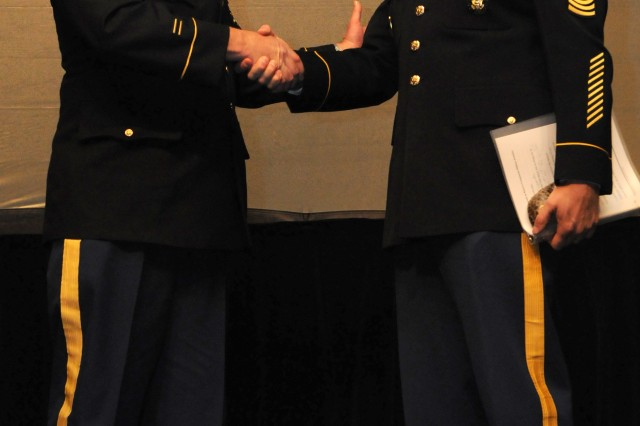 Command Sgt. Maj. Daniel G. Lincoln, Michigan National Guard Command Sgt. Maj., shakes the hand of Sgt. Maj. of the Army Raymond F. Chandler III after his speech during the National Research Summit on Reserve Component Military Families in Ann Arbor, Mich., April 25-26, 2013.