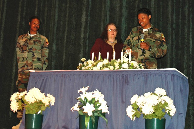(From left)  Military Youth Corps Freestate ChalleNGe Academy Cadet Ikea Green and Rabbi Gila Ruskin, from Temple Adas Shalom, look on as Cadet Dalanie Moore lights a candle in remembrance and in honor of lives affected by the Holocaust during the Days of Remembrance ceremony in the post theater April 16.