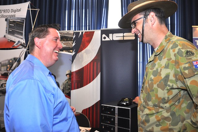 (From left) Steve Yosh, director of sales for NCS Technologies, Inc., talks multi-client stations with Australian Army Lt. Col. Matthew Kitchin, who is serving with the Communications-Electronics, Research, Development and Engineering Center, during the Spring Technology Expo at the APG North (Aberdeen) recreation center April 17.