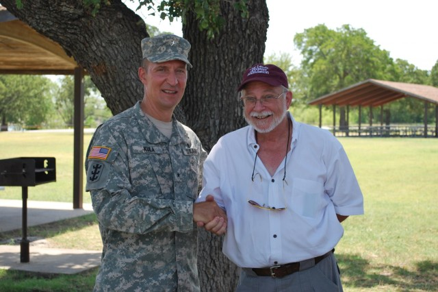 Brig. Gen. Thomas W. Kula, commander, Southwestern Division, U.S. Army Corps of Engineers, presents Tom Burrell, chief executive officer, Our Lands and Waters Foundation with a commander's coin for OLWF's support of a water safety day at Lewisville Lake.