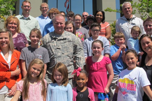 Col. Robert J. Ruch, Commander,  U.S. Army Engineering and Support Center, Huntsville poses with daughters and sons of Huntsville Center employees April 25.