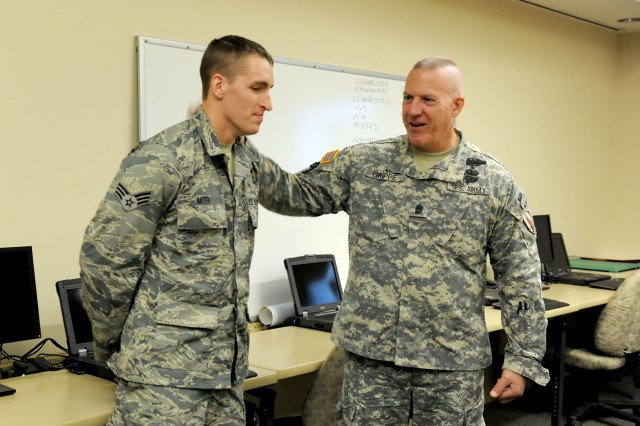 U.S. Central Command Army Command Sgt. Maj. Frank A. Grippe congratulates New York Air National Guard Senior Airman Jeremy Miter on his recent completion of Joint Tactical Air Controller (JTAC) training as a member of the 274th Air Support Operations Squadron at Hancock Field in Syracuse NY on April 18, 2013. Grippe was at Hancock Field to get an overview of the current operations of the 174th Attack Wing and the 27th Infantry Brigade Combat Team both of which are located on Hancock Field.