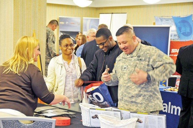 Meleana Heffner, staffing administrator, Russell Stover Candies, left, speaks with, from left to right, Dorothy Alleyne, military spouse, Chicago; Jeffery Williams, apprentice electrician, Indelible Impressions, Chicago; and Sgt. Ephraim Torres, 299th BSB, 2nd ABCT, April 16 at Riley's Conference Center, Fort Riley, Kan.