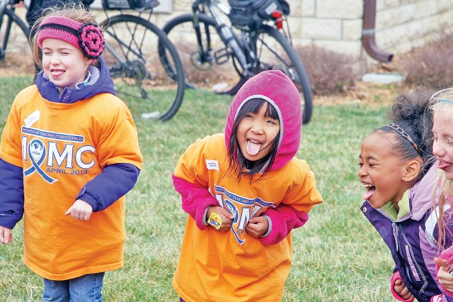 Children put their tongues out before putting their tongues in during a game of Hokey Pokey at the end of the MOMC Parade April 16 on Main Post, Fort Riley, Kan. Children sang songs and played games in Cavalry Parade Field, where the parade route ended.