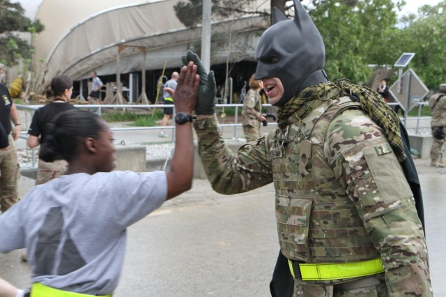 The Bagram Batman, Bagram Air Field's caped crusader for public safety, high-fives a runner during a 5k run celebrating the Army Reserve's 105th birthday April 25, 2013. More than 500 runners gathered for the early morning run. The Reserve, which was founded April 23, 1908, as a reserve corps of medical personnel, now includes 148 different military occupation specialties and accounts for 20 percent of the Army's total force. (U.S. Army National Guard photo by Spc. Mark VanGerpen, 129th Mobile Public Affairs Detachment)