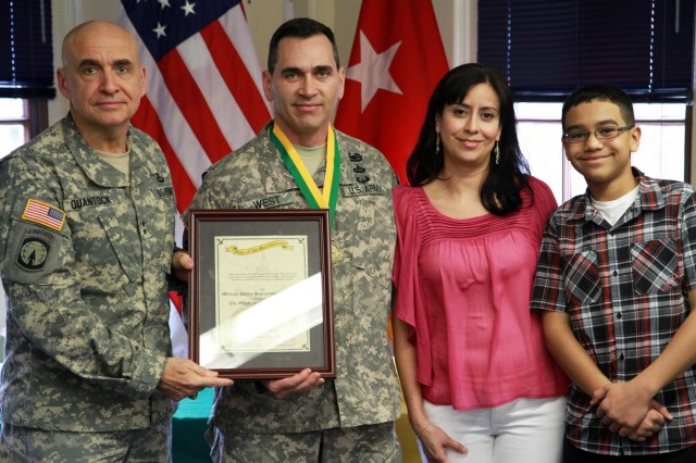 U.S. Army Maj. Gen. David E. Quantock, left, the provost marshal general of the Army, presents the Legend of the Order of the Marechaussee (Bronze) award to Sgt. Maj. Alan J. West, center, the I Corps provost marshal sergeant major, as his his wife, Isis, and son, Jeremy, look on, during a ceremony at Joint Base Lewis-McChord, Wash., April 17, 2013. (U.S. Army photo by Sgt. Jennifer Spradlin/Released)