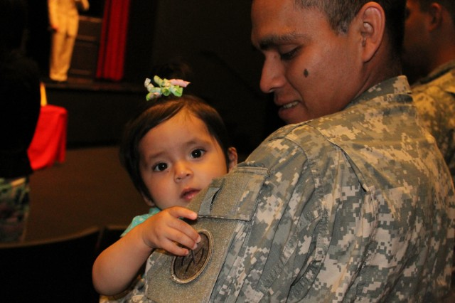 Spc. Frankie Aguilar of the 1st Battalion, 69th Infantry Regiment watches as his daughter Jadalyse plays with his unit patch during a Freedom Salute Ceremony April 28 in Queens, N.Y. Aguilar, a Brentwood resident, has just returned from serving in Kuwait. The ceremony, held 90 days after Soldiers returned to their homes, honored both returning Soldiers and the families, and employers friends who supported them. (U.S. Army Photos by Spc. J.p. Lawrence, 42nd Infantry Division).