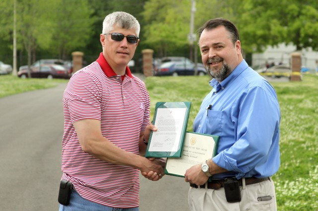 AMRDEC Director Eric Edwards presents Tim McDowell with a Department of the Army Certificate of Achievement, a personal note from RDECOM Director Dale A. Ormond and an AMRDEC director's coin on April 18.