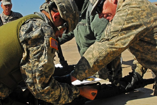 "Staff Sgt. Michael McHugh (right), armor crewman and Greenville, N.Y. native with Company D, 2nd ""Lancer"" Battalion, 5th Cavalry Regiment, 1st ""Ironhorse"" Brigade Combat Team, 1st Cavalry Division, instructs Pvt. DeSean Murphy, a Seattle native and armor crewman assigned to Company C, during Lancer's gunnery skills testing April 24, at Fort Hood, Texas. The test evaluated Murphy's performance of basic operations of the .50 caliber machine gun. (Photo by Pfc. Paige Pendleton, 1BCT Public Affairs, 1st Cav. Div.)"