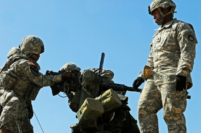 "Staff Sgt. Dallas Jackson (right), a Jonesboro, La. native and platoon sergeant assigned to 181st Chemical Company, 2nd Chemical Battalion, 48th Chemical Brigade, evaluates 1st Lt. Brittany Myatt (left), a Troy, Mich. native and chemical officer assigned to Headquarters and Headquarters Company, 1st ""Centurion"" Brigade Special Troops Battalion, 1st ""Ironhorse"" Brigade Combat Team, 1st Cavalry Division, during the 2nd ""Lancer"" Battalion's gunnery skills testing April 24, at Fort Hood, Texas. The event assessed the proficiency of Myatt's team in mounting an M2 .50 caliber machine gun to a weapon station on a Stryker Armored Fighting Vehicle. (Photo illustration by Pfc. Paige Pendleton, 1BCT Public Affairs, 1st Cav. Div.)"