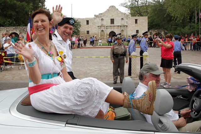 """SAN ANTONIO """" Lt. Gen. William Caldwell IV waves to the crowd as his wife, Stephanie, shows off her combat boots in front of the Alamo during the annual Battle of Flowers Parade April 26. Caldwell, the commanding general of U.S. Army North (Fifth Army) and senior commander of Fort Sam Houston and Camp Bullis, serves as the military coordinator for the Fiesta San Antonio 2013 events."""