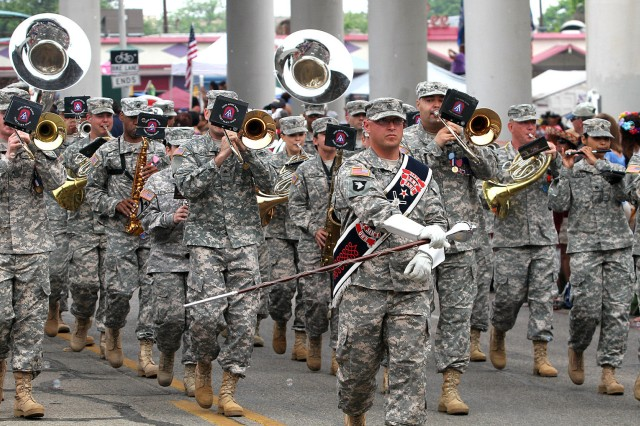 "SAN ANTONIO "" Members of the 323rd Army Band ""Fort Sam's Own"" belt out the tunes as they march down Broadway April 26 during the annual Battle of Flowers Parade. The theme for this year's event was ""Celebrations."" The parade is one of key events during Fiesta San Antonio."