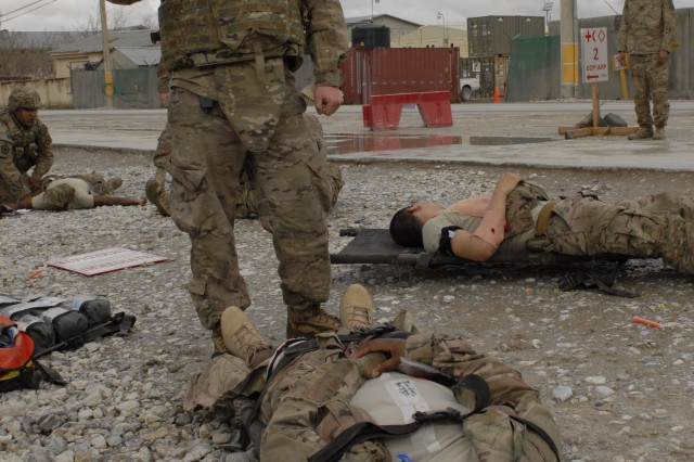 U.S. Army Spc. Joshua Adams, center, a medic with Headquarters and Headquarters Company, 555th Engineer Brigade, directs medical treatment and casualty evacuation as the triage officer during a company mass casualty training exercise at Bagram Airfield in Parwan province, Afghanistan, March 24, 2013.
