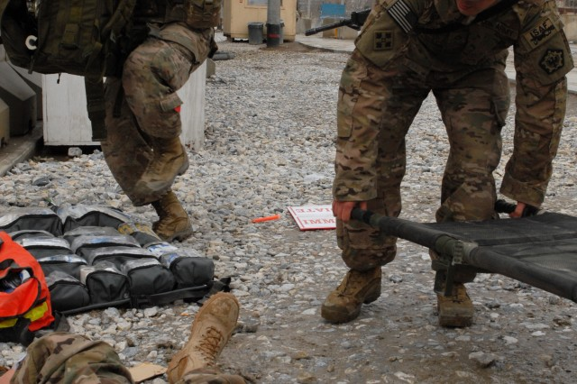 U.S. Army Pfcs. Moody Watson and Aaron Dreas, both with Headquarters and Headquarters Company, 555th Engineer Brigade, provide medical aid to Pfc. Morgan Tunell as she plays the part of a simulated casualty during a company mass casualty training exercise at Bagram Airfield in Parwan province, Afghanistan, March 24, 2013.