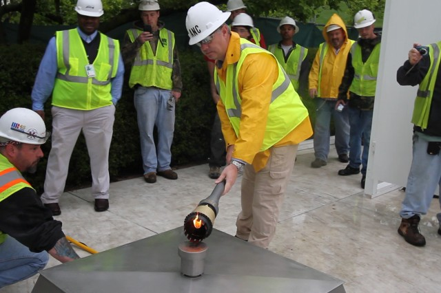 Randy Barton, an Arlington National Cemetery engineering technician, lights a temporary flame using a torch that was lit from the John F. Kennedy Eternal Flame at the cemetery April 29, 2013. The temporary flame will burn while the permanent flame undergoes repair and upgrade work to install new burners, a new igniter and new gas and air lines. Work on the burner itself will take about three weeks to complete. (U.S. Army photo/Patrick Bloodgood)
