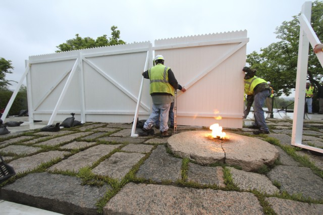 "ARLINGTON, Va. "" Contractors install white fencing  at the John F. Kennedy Eternal Flame at Arlington National Cemetery April 29, 2013. The fencing will block the public's view of the flame while contractors install burners, an igniter and new gas and air lines. Work on the burner itself will take about three weeks to complete. (U.S. Army photo/Patrick Bloodgood)"