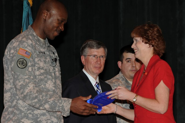 Col. Gordon Graham, ATC commander, presents the Commander's Leadership Award to Norma Yowell as John Wallace, ATC technical director, and Sgt. 1st Class Jessie Lopez, ATC noncommissioned officer in charge, look on during the ATC Annual Awards Ceremony at the Aberdeen Proving Ground Post Theater April 9, 2013.