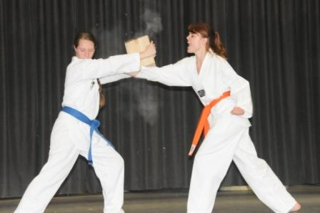 Albany Briley (R) shatters a pair of boards held by HTA Taekwondo teammate Jessica Roycroft during the Celebration of the Arts, April 20.