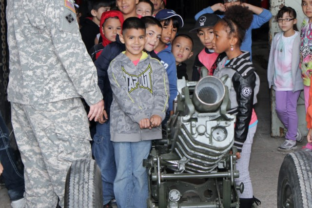 "FORT SAM HOUSTON, Texas "" Sgt. Jared Dunn explains the workings of ""Loyalty,"" a 75mm M1A1 pack howitzer, as second-graders from Sun Valley Elementary School practice pulling the firing handle during an April 25 field trip to the Army North stables. Army North has seven ceremonial howitzers; each is named for an Army value. Dunn serves as the flags and cannons section leader for U.S. Army North (Fifth Army)."