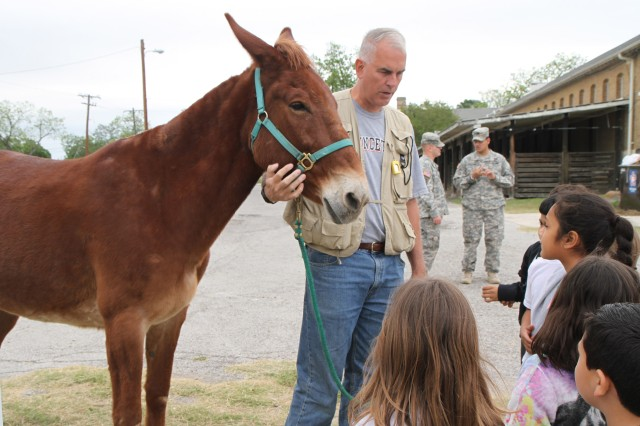 "FORT SAM HOUSTON, Texas "" Jim Boelens, a volunteer at the U.S. Army North (Fifth Army) stables, along with Scooter, the mule, teach second-graders from Sun Valley Elementary School about personal courage and other Army values April 25 during the students' field trip to the Army North stables. Mules are considered courageous animals for their predisposition to turn and face threats as opposed to running away."