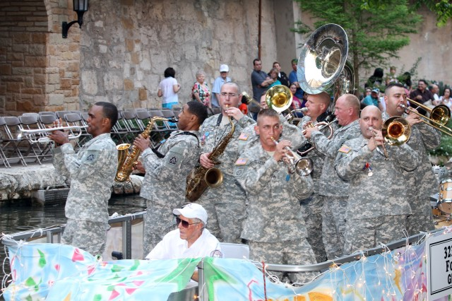 "SAN ANTONIO "" Members of the 323rd Army Band ""Fort Sam's Own"" belt out the tunes as they float down the river April 22 during the annual Texas Cavaliers River Parade. The theme for this year's event was ""Stars on the River."" The parade is one of key events during Fiesta San Antonio and dates back to 1941. It runs along the River Walk in downtown San Antonio."