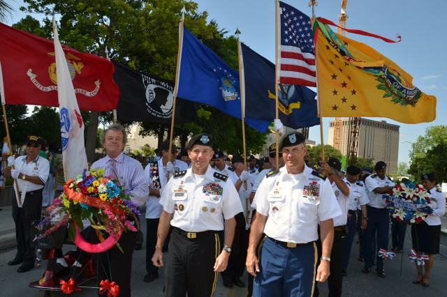 "FORT SAM HOUSTON, Texas "" James Fenimore (left), along with Lt. Gen William Caldwell IV and Command Sgt. Maj. Hu Rhodes, await the start of the Pilgrimage to the Alamo near the Municipal Auditorium while Vietnam veterans bearing various flags stand behind them April 22. The pilgrimage is one of the more somber events of Fiesta, an 11-day celebration across San Antonio. It features more than 100 different events focusing on the vibrant culture and rich history of the city. Caldwell is the commanding general of U.S. Army North (Fifth Army) and senior commander for Fort Sam Houston and Camp Bullis. Rhodes is his senior enlisted leader, and Fenimore is the Fiesta commissioner representing Vietnam veterans."