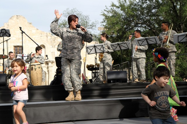 "SAN ANTONIO "" San Antonio children dance along with Sgt. Isis Rosario (center) and the 323rd Army Band ""Fort Sam's Own"" April 17 at the Alamo during Fiesta Fiesta. Rosario and the music ensemble ""Latin Invasion"" entertained the crowd with traditional Latin music. The band's music ensembles ""Latin Invasion,"" ""The Bio Hazard Brass Band"" and ""Texas Flood"" provided musical entertainment for the crowd throughout the evening. Rosario, who recently finished her nursing degree, is currently assigned to the U.S. Army Medical Department student detachment. She is attached to the 323rd until she receives her commission July 15."