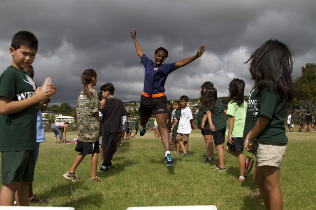 Sgt. Phillis White, the retention noncommissioned officer for the 8th Special Troops Battalion, 8th Theater Sustainment Command, leaps for joy during the Webling Elementary School Fall Festival, and annual event that she helps out with.  White has volunteered more than 1,120 hours of her time to helping the students and teachers of the school.