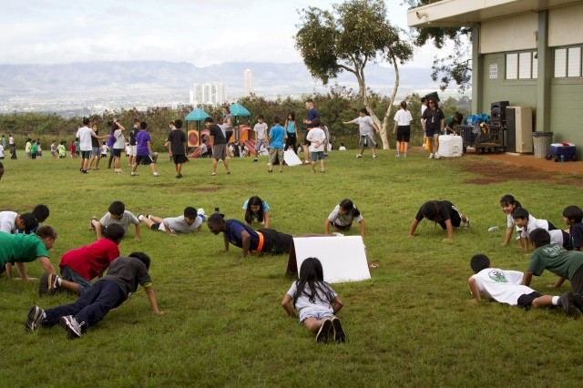 Sgt. Phillis White, the retention noncommissioned officer for the 8th Special Troops Battalion, 8th Theater Sustainment Command, demonstrates the proper way to do a push up to the students of Webling Elementary School in Aiea, Hawaii. She has volunteered more than 1,120 hours of her time to helping the students and teachers of the school.