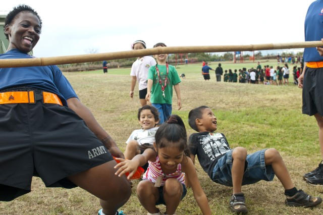 Sgt. Phillis White, the retention noncommissioned officer for the 8th Special Troops Battalion, 8th Theater Sustainment Command, limbos with the kids from Webling Elementary School in Aiea, Hawaii. She has volunteered more than 1,120 hours of her time to helping the students and teachers of the school.