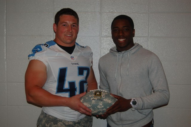 Tennessee Titans' fullback and Army Reserve 1st Lt. Collin Mooney presents an Army football to Bowling Green High School's Nacarius Fant, who was nominated to play in the Jan. 4, 2014, Army All-American Bowl in San Antonio.