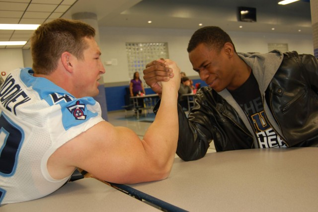Army Reserve 1st Lt. Collin Mooney, a fullback for the Tennessee Titans, arm wrestles with Tennessee High School Senior Ladarian Allison.