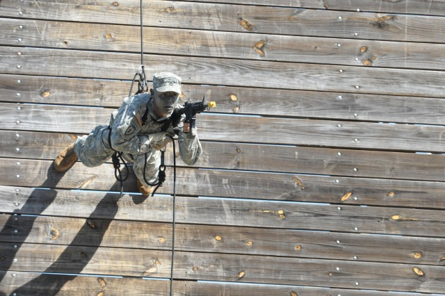 Staff Sgt. Cesar Hembree with 4th Ranger Training Battalion demonstrates the Australian rappel before the Ranger Class 5-13 graduation, April 26, 2013, at Fort Benning, Ga.  The Maneuver School of Excellence plans to functionally realign its brigades to streamline brigade structure, maximize efficiency and reduce redundancy.