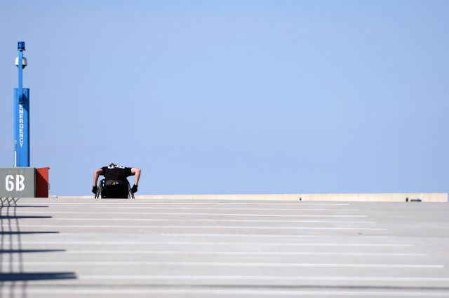 Maj. John Arbino pushes himself up to the top of the ramp of a parking deck at Fort Belvoir, Va., as he trains for the 2013 Warrior Games.