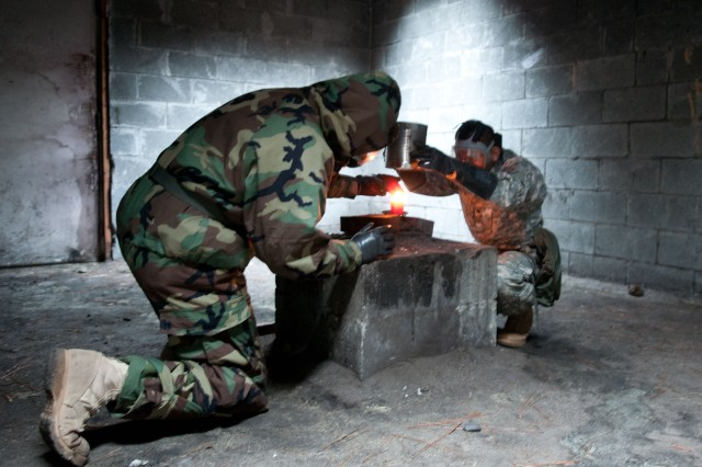 Sgt. Dan L. Adams of Rock Hill, S.C., and Spc. Diego R. Aguilar, from Ecuador, each serving as chemical, biological, radiological and nuclear specialists with the 82nd Airborne Division's 1st Brigade Combat Team, emplace a lit candle in a gas chamber, April 29, 2013, on Fort Bragg, N.C. The paratroopers used the candle to melt capsules of O-chlorobenzylidene-malononitirle, or CS gas, during annual gas chamber training held for White Devil soldiers.
