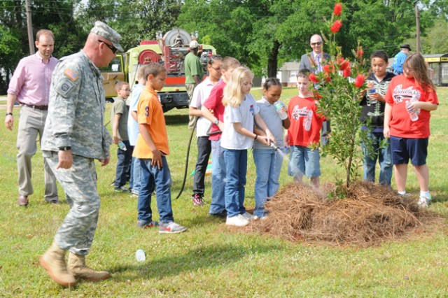 Command Sgt. Maj. Buford E. Noland, Fort Rucker garrison command sergeant major, and Justin O. Mitchell, Fort Rucker deputy garrison commander, look on as children from the Fort Rucker Elementary School water freshly planted trees they helped put in the ground behind the Fort Rucker Youth Center in celebration of Earth Day.