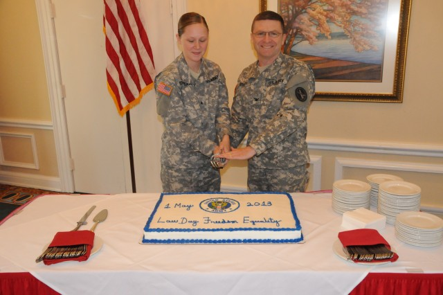 Sgt. Jessica R. Segobiano, U.S. Army Military District of Washington paralegal noncommissioned officer and Col. Corey L. Bradley, MDW's Office of the Staff Judge Advocate, cut the Law Day cake during a ceremony held at the Fort Lesley J. McNair Officer's Club, May 1.    Every May first, Americans celebrate Law Day, giving them an opportunity to reflect on the rule of law and the foundations of their legal system.  It's a time for citizens to celebrate the history of America's judicial system and to consider its future.