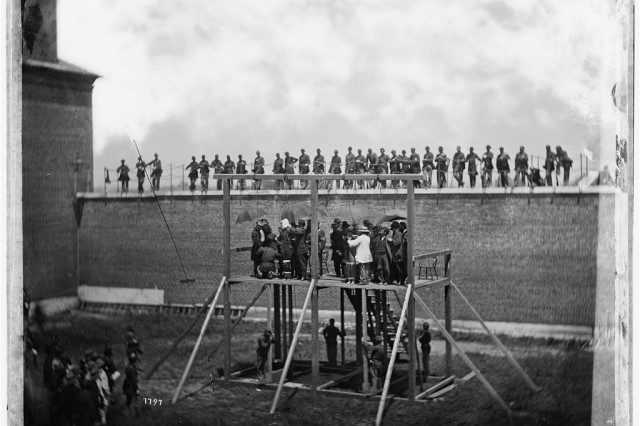 Officials adjust the ropes shortly before hanging the Lincoln conspirators from the scaffold at Fort Lesley J. McNair, July 7, 1865.  The commanding general of the Military District of Washington, Maj. Gen. Winfield Scott Hancock gave the order for the gibbet to be dropped.  While this courtyard no longer exists at Fort McNair, the building where the trial was held still remains.