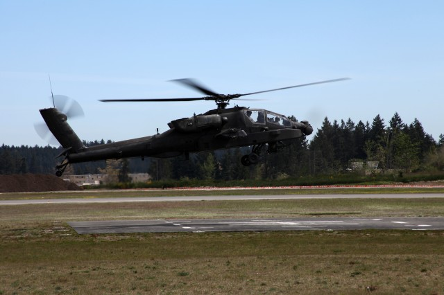 Chief Warrant Officer 4 Philip Hettich, 1-229th Attack Reconnaissance Battalion pilot, returns to Gray Army Airfield at Joint Base Lewis-McChord in an AH-64D Apache helicopter May 2 from his final flight prior to retirement. Upon completing taxiing, he was drenched with a fire hose per aviation tradition.