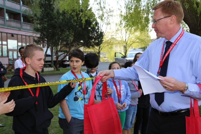 "Paul Howard, chief of Operations, Plans and Security for the U.S. Army Corps of Engineers Europe District, hands out gift bags to Wiesbaden Middle School students April 25 during ""Take Your Child to Work Day"" at the Amelia Earhart Center in Wiesbaden, Germany."