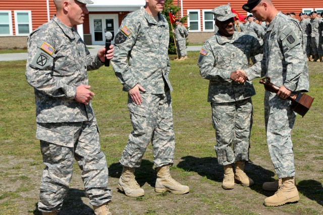 From right, U.S. Army Sgt. 1st Class Thomas A. Robinson, the fire control chief and digital master gunner with 1st Battalion, 377th Field Artillery Regiment, 17th Fires Brigade, shakes hands with Command Sgt. Maj. Edward E. Russell, the 17th Fires Brigade senior enlisted adviser, after Robinson received the Edmund L. Gruber Award during an award ceremony at Joint Base Lewis-McChord, Wash., April 30, 2013. The Gruber award is named after Brig. Gen. Edmund L. Gruber, who composed the official Army song, and is awarded to an individual soldier each year for significant contributions and innovative enhancements to the field artillery corps. (U.S. Army photo by Spc. Nathan Goodall/Released)