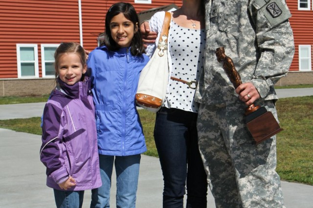 From right, U.S. Army Sgt. 1st Class Thomas A. Robinson, the fire control chief and digital master gunner with 1st Battalion, 377th Field Artillery Regiment, 17th Fires Brigade, with his wife Jennifer and two of their daughters, after Robinson was presented with the Edmund L. Gruber Award at Joint Base Lewis-McChord, Wash., April 30, 2013. The Gruber award is named after Brig. Gen. Edmund L. Gruber, who composed the official Army song, and is awarded to an individual soldier each year for significant contributions and innovative enhancements to the field artillery corps. (U.S. Army photo by Spc. Nathan Goodall/Released)