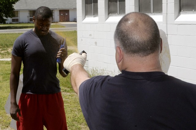 Security guard Shasta Williams (left) had to issue and simulated emergency call after Department of the Army police training officer Lt. Ronald Henson sprayed him with pepper spray.
