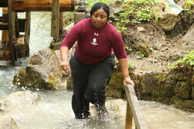 """Spc. Dawanda Corey of A Company, Warrior Transition Battalion-Europe, navigates the """"natural foot massage"""" obstacle during The Amazing Race competition held in Garmisch, May 1."""