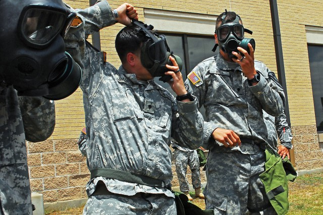 "Spc. Patrick Maurer (left), a cavalry scout native to San Antonio, and Spc. Daniel Felix (right), an infantryman native to Modesto, Calif., both assigned to Headquarters and Headquarters ""Hammer"" Troop, 1st ""Ironhorse"" Brigade Combat Team, 1st Cavalry Division, practice donning and sealing their protective masks in nine seconds during chemical, biological, radiological and nuclear training May 1 at Fort Hood, Texas. (Photo by Pfc. Paige Pendleton, 1st BCT, 1st Cav. Div. Public Affairs)"