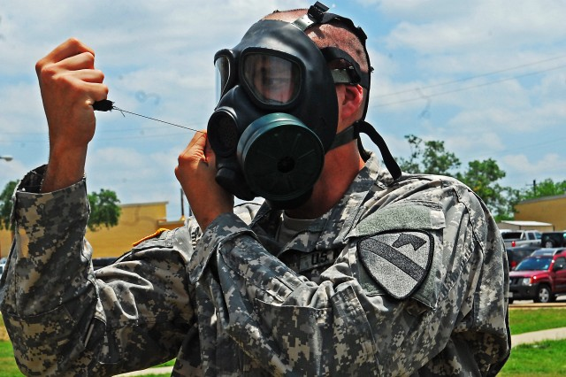 "Midland, Mich. native, Cpt. Timothy Martin, commander of Headquarters ""Hammer"" Troop, 1st ""Ironhorse"" Brigade Combat Team, 1st Cavalry Division, discovers a defect in his protective mask during chemical, biological, radiological and nuclear training May 1 at Fort Hood, Texas. The semi-annual classes are conducted to ensure Soldiers know how to properly use their equipment. (Photo by Pfc. Paige Pendleton, 1st BCT, 1st Cav. Div. Public Affairs)"