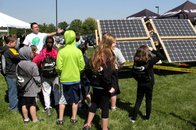 Chemical Engineer Cao Chung talks to students about how CERDEC's Renewable Energy for Distributed Under-Supplied Command Environments, or REDUCE, trailer provides power for Soldiers during the APG Earth Day and Arbor Day event at the APG North (Aberdeen) youth center April 26.